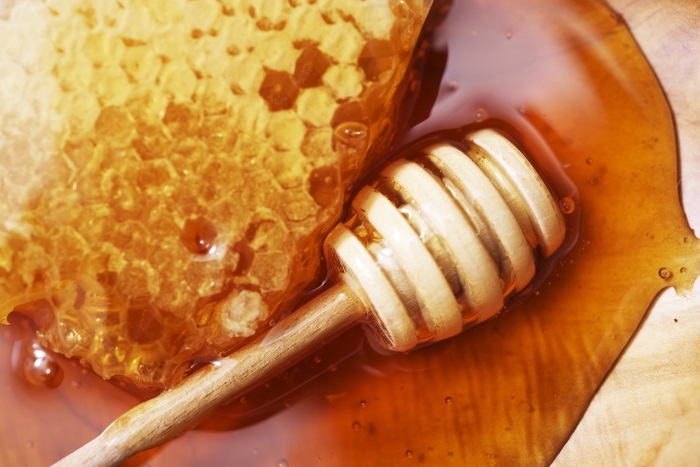 Honeycomb with Wooden Dipper on Wooden Plate Closeup
