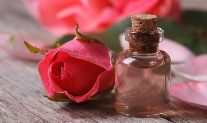 a bottle of rose water with a rose